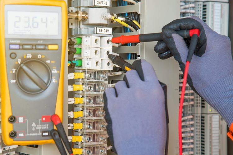 electrician measuring an electrical panel